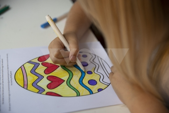 Girl colouring in easter egg drawing - stock photo