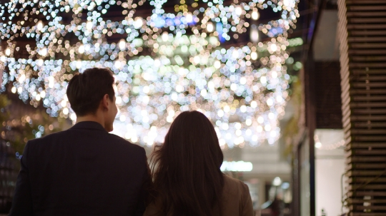 Couple walk under fairy lights - stock video
