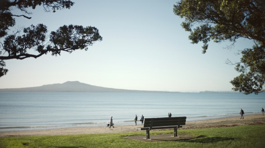 Beach scene with walkers and park bench - stock video