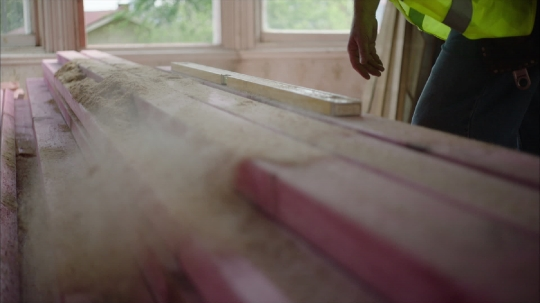 Slow motion shot of builder brushing sawdust of timber - stock video