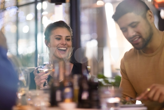 Friends laughing at dinner - stock photo